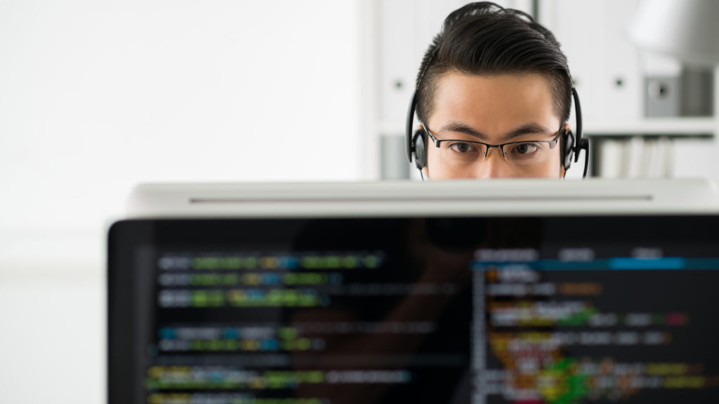 Young Asian man in headset and glasses working with computer and programming