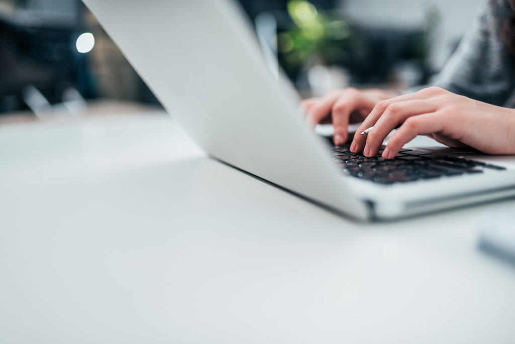 Female person typing on laptop. Close-up, copy space.